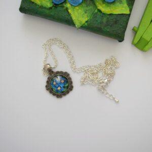 Üveglencsés nyaklánc - ötszög - Pillangó kék virágokon